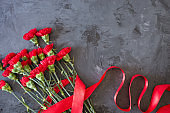 red carnations on grey/black background, Flat lay, Top view with copy space