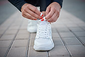 Woman get ready for run. Female hands tying shoelaces on a sport sneakers