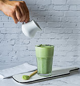 Matcha green tea latte with matcha powder and wooden spoon .