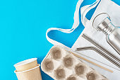 Zero waste concept. Eco friendly reusable items on natural shopping bag. Paper egg tray, coffee cups, aluminum bottle and metal tubes on a blue background