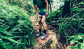 Woman trail runner spraying insect repellents on skin in summer tropical forest
