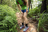 Woman trail runner spraying insect repellents on skin in summer tropical rainforest