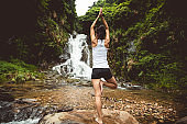Young woman practice yoga near waterfall in forest