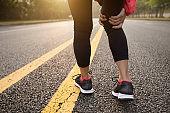 Running sport injury female runner touching sprained ankle