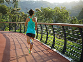 Runner athlete running on spring forest trail. woman fitness jogging workout wellness concept.