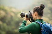 woman photographer taking photo on spring forest mountain
