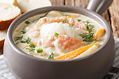 Norwegian creamy fish soup fiskesuppe with cod and salmon closeup. horizontal