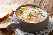 Closeup of creamy fish soup with cod, salmon, carrot and celery in a bowl served with fresh bread. horizontal