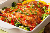 baked salmon with summer vegetables close-up in a baking dish. horizontal