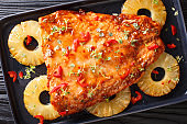Baked Thai pineapple salmon in a sour-sweet sauce closeup on a plate. horizontal top view
