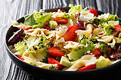 Italian pasta farfalle with avocado, strawberries, lettuce and balsamic sauce close-up on a plate. horizontal