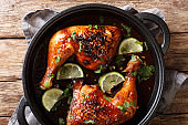 quarter chicken leg baked with tamarind sauce and lime closeup in a pan. horizontal top view