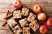 Homemade apple blondies with cinnamon and nuts close-up on a slate board. Horizontal top view