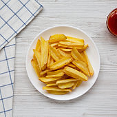 Homemade french fries with sour-sweet sauce on a white plate on a white wooden table, top view. Flat lay, overhead, from above. Close-up.
