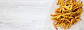 Homemade french fries on a white wooden background, top view. Flat lay, overhead, from above. Copy space.