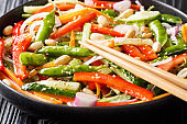 Asian salad of carrots, peas, peppers, cucumbers and onions close-up on a plate. horizontal