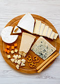 Tasting delicious cheese with  walnuts, bread sticks and pretzels on bamboo board, top view. Food for wine. From above. Flat lay. Copy space.