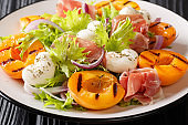 Italian salad with mozzarella, prosciutto, grilled apricots, red onion and  lettuce close-up on a plate. horizontal