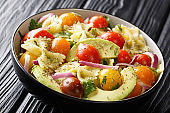 Pasta farfalle with ripe avocado, onions and tomatoes with spicy sauce closeup in a bowl. horizontal
