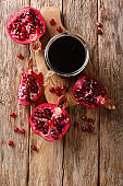 Delicious spicy pomegranate sauce narsharab with spices for seasoning meat dishes close-up. Vertical top view