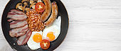 Full English Breakfast in cooking pan with sausages, fried eggs, beans and bacon on a white wooden table, top view. Copy space. From above. Flatlay.
