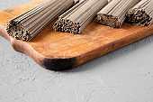 Dried buckwheat soba noodles on rustic wooden board over gray surface, side view. Close-up.