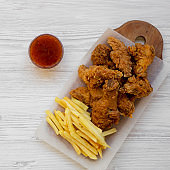 Fastfood: fried chicken drumsticks, spicy wings, French fries and chicken fingers with sour-sweet sauce over white wooden surface, top view. Flat lay, overhead, from above. Close-up.