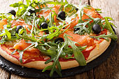 Salmon pizza with fresh arugula, black olives and cheese closeup. horizontal