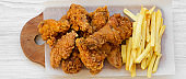 Tasty fastfood: fried chicken drumsticks, spicy wings, French fries and chicken strips over white wooden background, top view. Flat lay, overhead, from above.