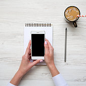 Smartphone in female hands. Feminine workspace with notepad and latte ice. Top view. From above.