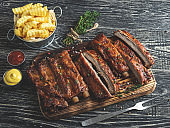 grilled pork ribs with sauce on a cutting board, french fries