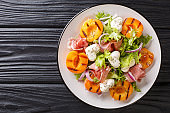 Easy dietary salad with mozzarella, prosciutto, grilled apricots, red onion and lettuce close-up on a plate. horizontal top view