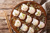 Traditional Chinese dim sum with shrimp filling served with sprouts close-up on a plate. horizontal top view