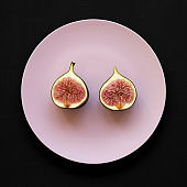 Fresh fig on a pink plate over black background, top view. Flat lay, overhead, from above.