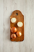 Unpeeled raw organic golden onions on rustic wooden board over white wooden background, top view. Flat lay, overhead, from above.