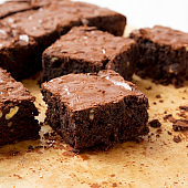 Home-baked chocolate brownies on a baking sheet, side view. Closeup.
