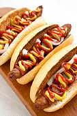 Homemade hot dogs with chicken sausage, ketchup and mustard on a rustic wooden board on a white wooden table, low angle view. Closeup.
