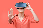 Young woman wearing virtual reality goggles. Woman wearing VR glasses over coral background. VR experience concept.