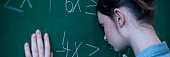 Teenager girl in math class overwhelmed by the math formula. Pressure, Education, Success concept. Student with head against blackboard.
