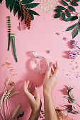 Transparent perfume bottle in flowers on pink background with woman's hands. Spring background with aroma parfume. Flat lay