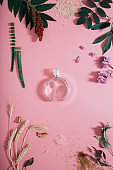 Transparent perfume bottle in flowers on pink background. Spring background with aroma parfume. Flat lay