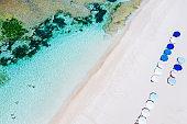 Beach umbrellas and blue ocean. Beach scene from above