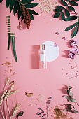 Mockup of bottle in flowers on pink background with white circle shape. Spring background with spa composition. Flat lay