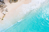 Beach scene from above - blue ocean and white sand beach with huge rocks. Aerial drone shot.