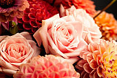 Floral composition of dahlia flowers, roses and autumn leaves.
