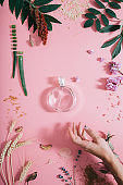 Transparent perfume bottle in flowers on pink background with woman's hand. Spring background with aroma parfume. Flat lay