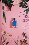 Perfume bottle with blue sticker in flowers on pink background. Spring background with aroma parfume. Flat lay