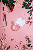 Transparent perfume bottle in flowers on pink background with white circle shape. Spring background with aroma parfume. Flat lay