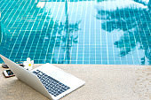 Laptop and smartphone near the swimming pool, modern businessman can work anywhere.