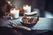 Burning candles and natural decor of cones, nuts in black bowl on the gray fabric napkin on the black table. Cozy atmosphere at home. Kinfolk Hygge Slow Living Style. Dark interior details concept.